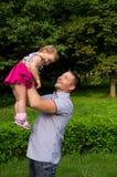 Le père heureux a jeté en l'air vers le haut de la fille Photo stock