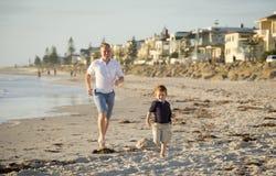Le père heureux jouant sur la plage avec le petit fonctionnement de fils excité avec nu-pieds dedans poncent et arrosent image libre de droits