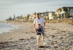 Le père heureux jouant sur la plage avec le petit fonctionnement de fils excité avec nu-pieds dedans poncent et arrosent images stock