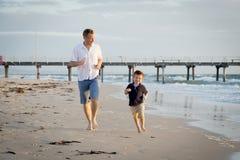 Le père heureux jouant sur la plage avec le petit fonctionnement de fils excité avec nu-pieds dedans poncent et arrosent photo libre de droits