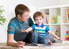 Le père heureux a lu un livre à l'enfant photo stock