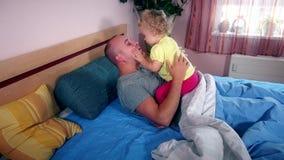 Le père heureux a passé le temps avec sa fille sur le lit dans la chambre à coucher banque de vidéos