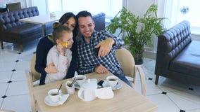 Le père heureux prend la photo de selfie avec son épouse et fille pendant leur temps de thé dans le café ou le restaurant Photographie stock libre de droits