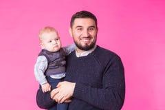 Le père heureux tenant le fils de bébé remet dedans le fond rose Photos libres de droits