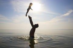 Le père jette en l'air vers le haut d'un enfant image libre de droits