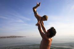 Le père jette en l'air vers le haut d'un enfant photos libres de droits
