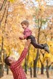 Le père jette la haute de garçon  Le père et le fils jouent et ont l'amusement en parc de ville d'automne Ils posant, sourire, jo photographie stock libre de droits