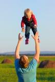 Le père jette son bébé heureux dans le ciel Amour et bonheur Image libre de droits
