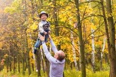 Le père jette son fils riant heureux dans le ciel en parc d'automne Photos libres de droits