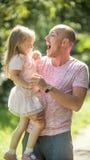 Le père joue avec ses petites filles en parc, jour d'été Images stock