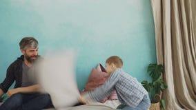 Le père joyeux de soin joue avec son petit fils, oreillers de combat, rit et apprécie des moments heureux aimer clips vidéos