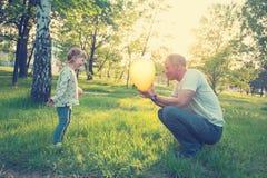 Le père joyeux et la petite fille de sourire jouent avec la couleur Photo stock