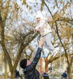 Le père joyeux jette sa fille en l'air  Marchent la famille en parc en automne photographie stock