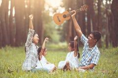 Le père, la mère et deux filles de petit enfant soulèvent leur main Images stock