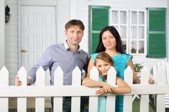 Le père, la mère et la fille heureux se tiennent à côté de la barrière blanche Image libre de droits