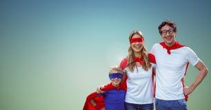 Le père, la mère et le fils dans le super héros costument la position sur le fond vert Photographie stock