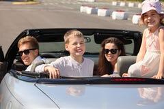 Le père, la mère et les enfants s'asseyent dans le véhicule convertible Photos stock