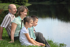 Le père, la mère, le garçon et la fille s'assied près de l'étang Images stock
