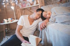 Le père lisait des contes de fées réservent à son fils la nuit à la maison L'homme et le garçon dorment photos libres de droits