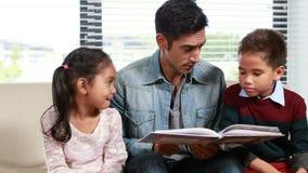Le père lisant le sien badine une histoire banque de vidéos