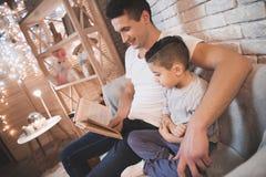 Le père lit des contes de fées réservent à son fils la nuit à la maison Image stock