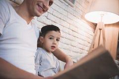 Le père lit des contes de fées réservent à son fils la nuit à la maison Photo libre de droits