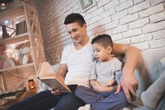 Le père lit des contes de fées réservent à son fils la nuit à la maison Photos stock