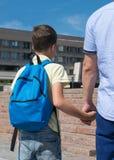 Le père mène un enfant à l'école sur des prises de classes sa main photo stock