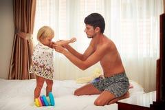 le père met dessus la robe à la fille par la fenêtre lumineuse Photographie stock