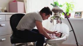 Le père a mis le bébé dans le berceau banque de vidéos