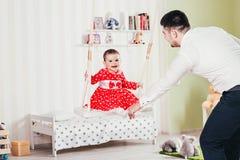 Le père monte sa fille sur une oscillation Une fille an dans une robe rouge s'assied sur une oscillation avec son papa Photos stock