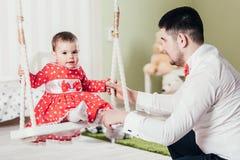 Le père monte sa fille sur une oscillation Une fille an dans une robe rouge s'assied sur une oscillation avec son papa Image libre de droits