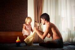 le père montre la nouvelle robe à la petite fille sur le sofa Photographie stock
