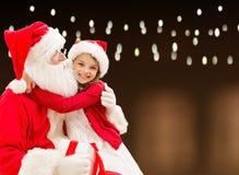 Le père noël avec le cadeau de Noël et la fille heureuse Photo libre de droits