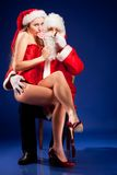 Le père noël avec la fille sexy dans le chapeau de Santa. Images libres de droits