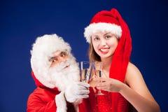 Le père noël avec la fille sexy dans le chapeau de Santa. Photos stock