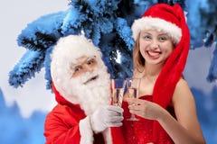 Le père noël avec la fille sexy dans le chapeau de Santa. Photographie stock