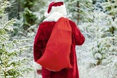 Le père noël avec le sac de cadeau dans la forêt Image stock