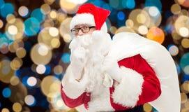 Le père noël avec le sac de cadeaux au-dessus des lumières de Noël Photographie stock