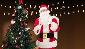 Le père noël avec le sac et l'arbre de Noël Photo libre de droits
