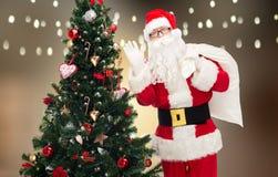 Le père noël avec le sac et l'arbre de Noël Photos stock