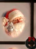 Le père noël dans l'hublot avec Bell argentée Image stock