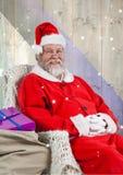 Le père noël de sourire s'asseyant avec le sac à cadeau Photographie stock libre de droits