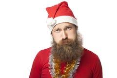 Le père noël drôle malheureux avec la vraie barbe et le chapeau et la chemise rouges regardant l'appareil-photo avec tristesse D' photo libre de droits