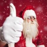 Le père noël enthousiaste faisant le signe correct tout en neigeant Photo stock