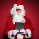 Le père noël est se tenant et lisant sur un ordinateur de protection de comprimé Photographie stock libre de droits
