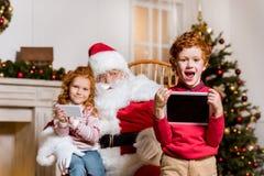 Le père noël et enfants avec les dispositifs numériques photos libres de droits