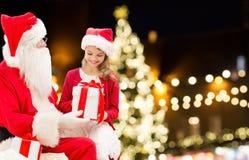 Le père noël et fille heureuse avec le cadeau de Noël Photographie stock