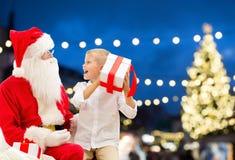 Le père noël et garçon heureux avec le cadeau de Noël Image libre de droits