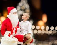 Le père noël et garçon heureux avec le cadeau de Noël Photos libres de droits
